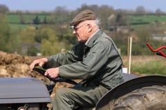 L'agricoltore anziano sul massey grigio fergusen il trattore alla partita d'aratura Immagini Stock Libere da Diritti