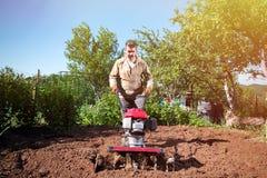 L'agricoltore ara la terra con un coltivatore, preparante la per il planti Immagini Stock Libere da Diritti