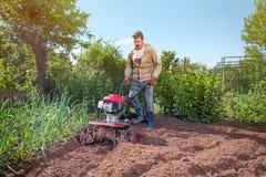 L'agricoltore ara la terra con un coltivatore, preparante la per il planti Fotografie Stock