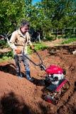 L'agricoltore ara la terra con un coltivatore, preparante la per il planti Fotografie Stock Libere da Diritti