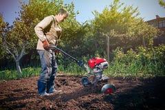 L'agricoltore ara la terra con un coltivatore, preparante la per il planti Fotografia Stock