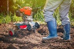 L'agricoltore ara la terra con un coltivatore, preparante la per il planti Fotografia Stock Libera da Diritti