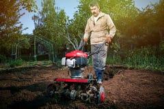 L'agricoltore ara la terra con un coltivatore, preparante la per il planti Immagine Stock Libera da Diritti