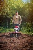 L'agricoltore ara la terra con un coltivatore, preparante la per il planti Immagine Stock