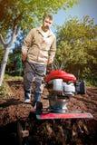 L'agricoltore ara la terra con un coltivatore, preparante la per il planti Immagini Stock