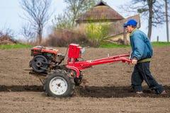 L'agricoltore ara la terra con un coltivatore, preparante la per la piantatura delle verdure fotografia stock libera da diritti