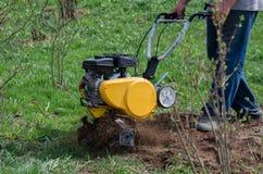 L'agricoltore ara la terra con un motoblock Il coltivatore allenta la terra fotografia stock libera da diritti