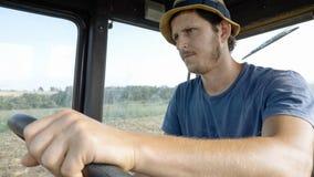 L'agricoltore in cappello, si siede dentro nella cabina del trattore, guida sul campo con l'aratro Fotografia Stock