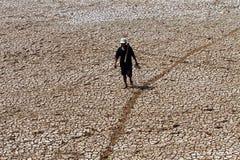 L'agricoltore che cammina fra il suolo asciuga dovuto un droug prolungato Fotografia Stock Libera da Diritti