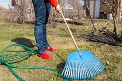 L'agricoltore che lavora nel giardino, rastrello della giovane donna rimuove il prato inglese, strumenti di giardino Fotografie Stock Libere da Diritti