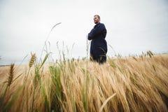 L'agricoltore che sta con le armi ha attraversato nel campo Immagine Stock Libera da Diritti