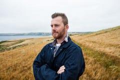 L'agricoltore che sta con le armi ha attraversato nel campo Fotografie Stock