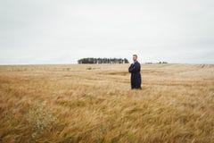 L'agricoltore che sta con le armi ha attraversato nel campo Fotografia Stock