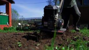 L'agricoltore coltiva la terra con un coltivatore archivi video