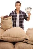 L'agricoltore con i sacchi ha riempito di chicchi di caffè che tengono i pacchi dei soldi Immagini Stock