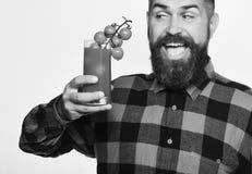 L'agricoltore con il fronte felice mostra il mazzo di pomodori ciliegia rossi L'uomo con la barba tiene il vetro del succo di pom Immagini Stock