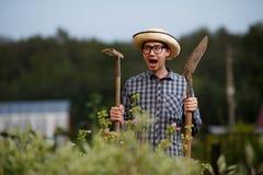 L'agricoltore con la pala ed il rastrello che gridano all'azienda agricola lavorano Fotografia Stock Libera da Diritti