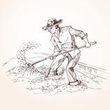L'agricoltore con una pala alza il grano Fotografia Stock Libera da Diritti