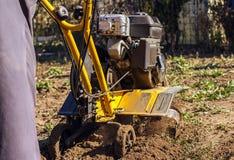 L'agricoltore del coltivatore ara la terra prima della piantatura Fotografia Stock