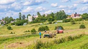 L'agricoltore dell'uomo gira il fieno nel rimorchio con una forca La Lituania Vilniu Fotografie Stock Libere da Diritti