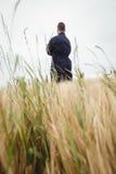 L'agricoltore di retrovisione che sta con le armi ha attraversato nel campo Immagine Stock Libera da Diritti