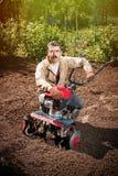 L'agricoltore felice dell'uomo ara la terra con un coltivatore, preparante la Immagine Stock Libera da Diritti