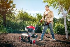 L'agricoltore felice dell'uomo ara la terra con un coltivatore, preparante la Immagini Stock