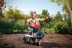 L'agricoltore felice dell'uomo ara la terra con un coltivatore, preparante la Fotografia Stock