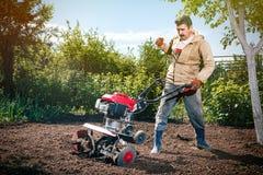 L'agricoltore felice dell'uomo ara la terra con un coltivatore, preparante la Fotografia Stock Libera da Diritti