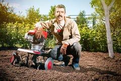 L'agricoltore felice dell'uomo ara la terra con un coltivatore, preparante la Fotografie Stock Libere da Diritti