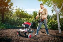 L'agricoltore felice dell'uomo ara la terra con un coltivatore, preparante la Fotografie Stock