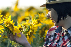 L'agricoltore femminile op vicino è nel campo con i girasoli Immagine Stock Libera da Diritti