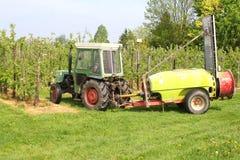 L'agricoltore lavora con il trattore e la macchina nel frutteto di frutta Fotografie Stock Libere da Diritti