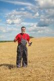 L'agricoltore o l'agronomo ispeziona nel giacimento di grano dopo il raccolto Immagini Stock