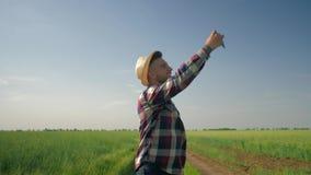 L'agricoltore prende il selfie sul telefono cellulare con le emozioni felici poi esamina lo schermo dell'aggeggio mentre cammina  video d archivio
