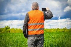 L'agricoltore prende le immagini sullo Smart Phone vicino al giacimento di cereale verde Immagine Stock Libera da Diritti