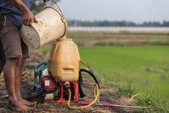 L'agricoltore prepara il prodotto chimico al carro armato dello spruzzatore prima di spruzzo per inverdirsi il yo Immagine Stock
