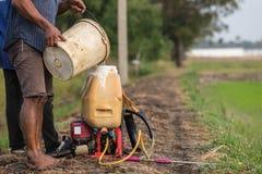 L'agricoltore prepara il prodotto chimico al carro armato dello spruzzatore prima di spruzzo per inverdirsi il yo Fotografie Stock
