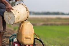 L'agricoltore prepara il prodotto chimico al carro armato dello spruzzatore prima di spruzzo per inverdirsi il yo Fotografia Stock Libera da Diritti