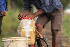 L'agricoltore prepara il prodotto chimico al carro armato dello spruzzatore prima di spruzzo per inverdirsi il yo Immagini Stock