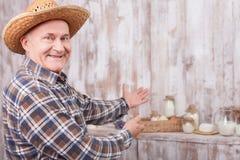 L'agricoltore senior allegro sta presentando il suo lavoro Fotografia Stock
