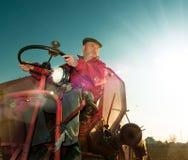 L'agricoltore senior determina la mietitrice, immagine tonificata Fotografia Stock Libera da Diritti
