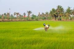 L'agricoltore sta spruzzando il fertilizzante Fotografie Stock Libere da Diritti