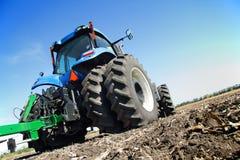 L'agricoltore su un trattore ha arato il campo Immagini Stock