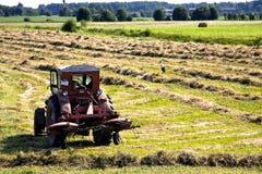 L'agricoltore su un trattore sta invertendo un fieno Fotografia Stock