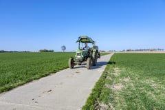 L'agricoltore sul suo trattore guida indietro dopo l'aratura del suo campo Fotografie Stock