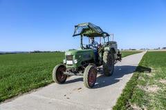 L'agricoltore sul suo trattore guida indietro dopo l'aratura del suo campo Fotografie Stock Libere da Diritti