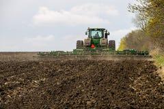 L'agricoltore sul trattore tratta il campo sulla molla Immagini Stock Libere da Diritti