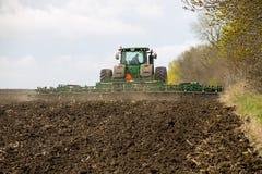 L'agricoltore sul trattore tratta il campo sulla molla Fotografia Stock