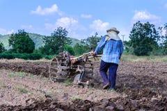 L'agricoltore tailandese che per mezzo dei motocoltivatori per il suolo coltivato per prepara la piantagione Immagine Stock
